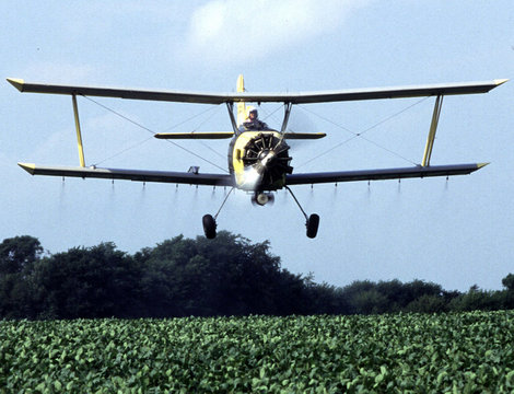 An airplane spreads fertilizer on a field