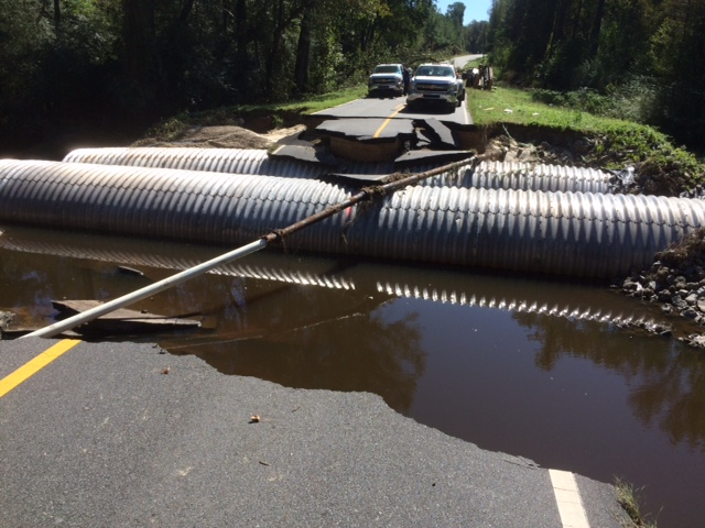 A photo of a damaged road with drainage pipes exposed